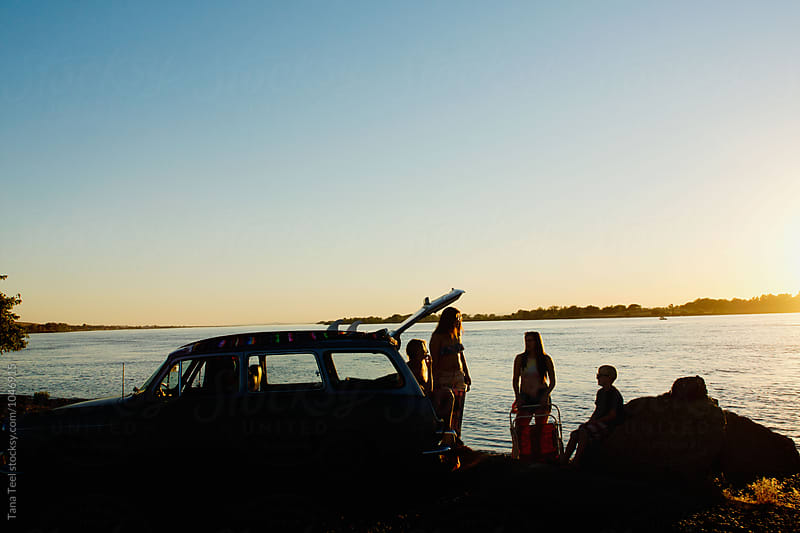 car and people silhoutted against setting sun by river by Tana Teel for Stocksy United