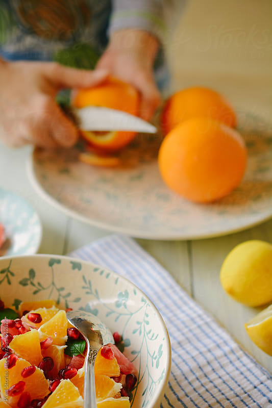 Woman slicing oranges by Pixel Stories for Stocksy United
