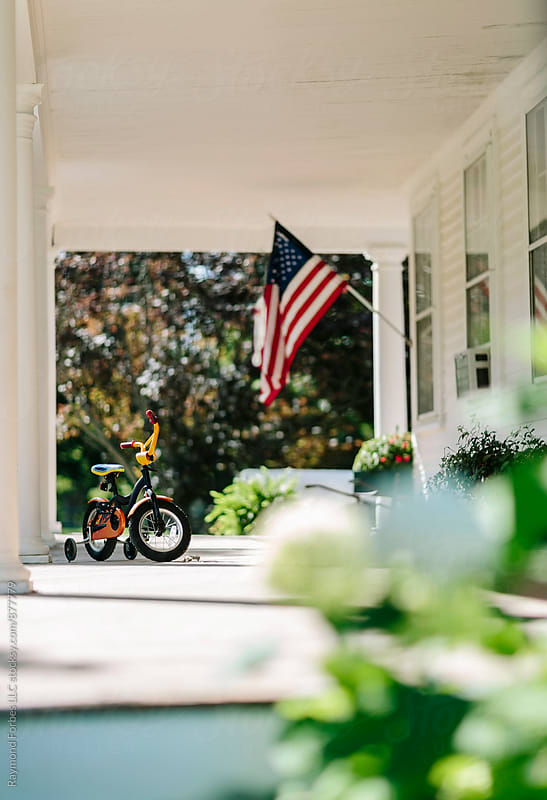 Front Porch of Home with American Flag by Raymond Forbes LLC for Stocksy United