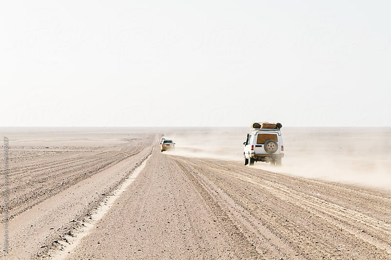 Off road vehicles crossing the desert on a sand road by Alejandro Moreno de Carlos for Stocksy United
