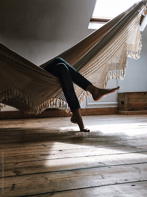 Girl relaxing in indoor hammock by Kirstin Mckee for Stocksy United