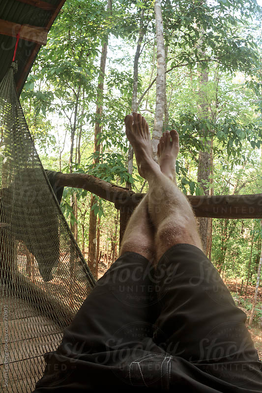 Legs of a person laying in a hammock outside with forest view by Soren Egeberg for Stocksy United