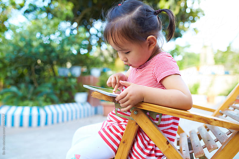 little asian girl playing with tablet in the garden by cuiyan Liu for Stocksy United