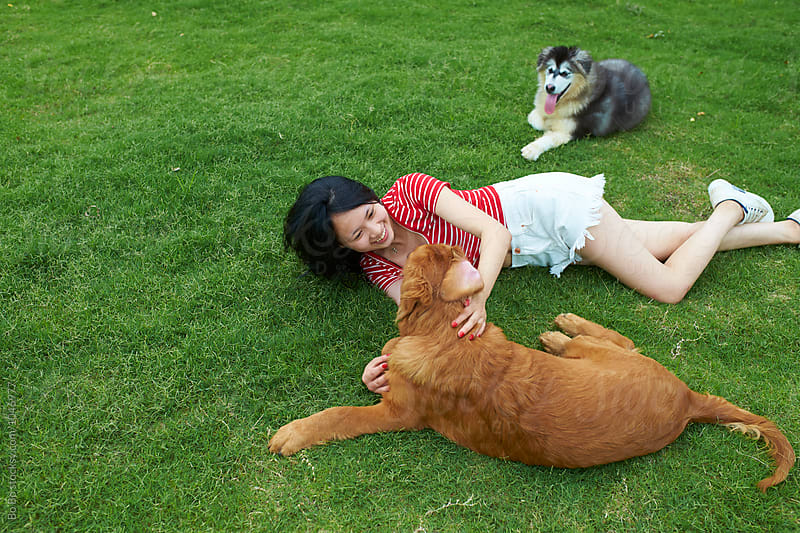 happy young woman with her dog outdoor by cuiyan Liu for Stocksy United