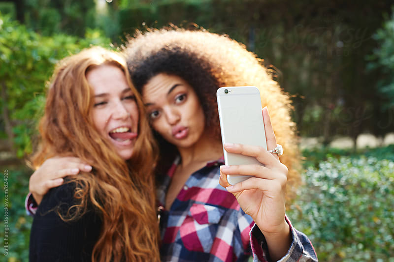 Best girlfriends taking selfie and making faces by Guille Faingold for Stocksy United