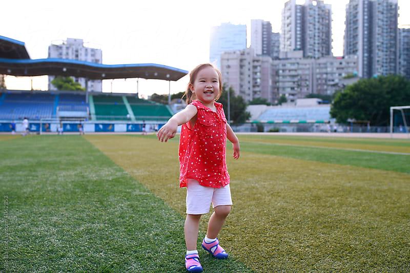 happy little girl outdoor in football field by Bo Bo for Stocksy United