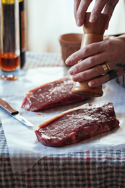 Seasoning meat. by Darren Muir for Stocksy United