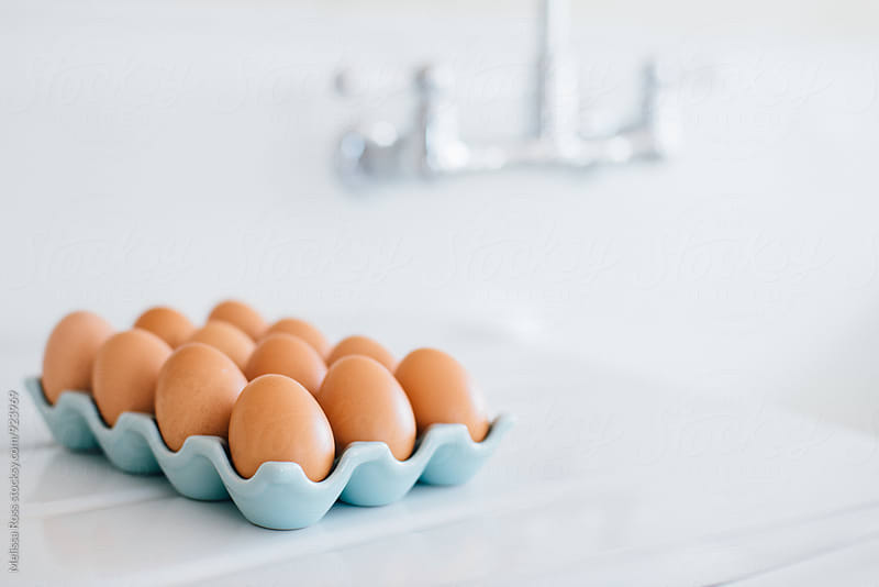 Brown chicken eggs displayed on an enamel countertop by Melissa Ross for Stocksy United