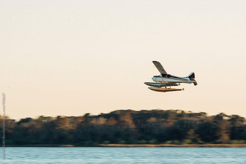 Seaplane taking off over a lake by Gabriel (Gabi) Bucataru for Stocksy United