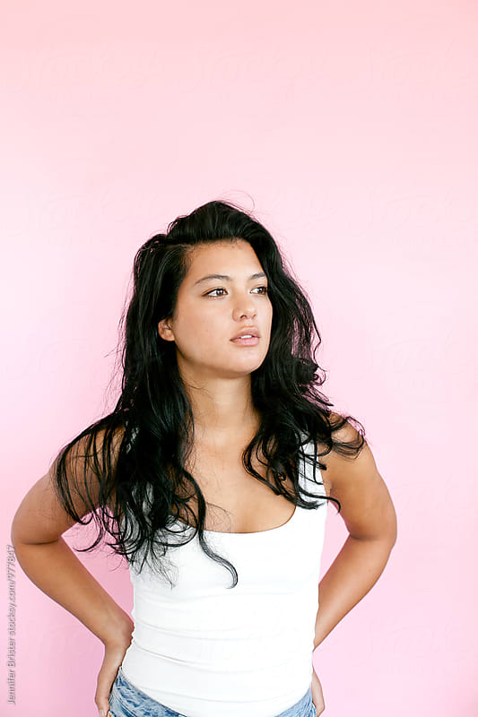 Attractive young woman with pink background by Jennifer Brister for Stocksy United