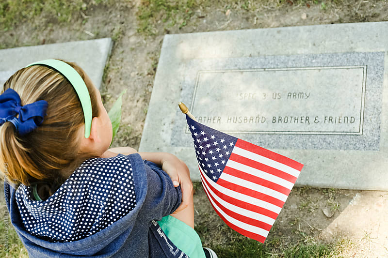 Little girl paying respect at a gravestone on Memorial Day by Carolyn Lagattuta for Stocksy United