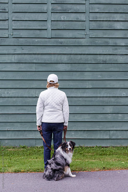 A woman and her dog stand in front of a barn. by Holly Clark for Stocksy United