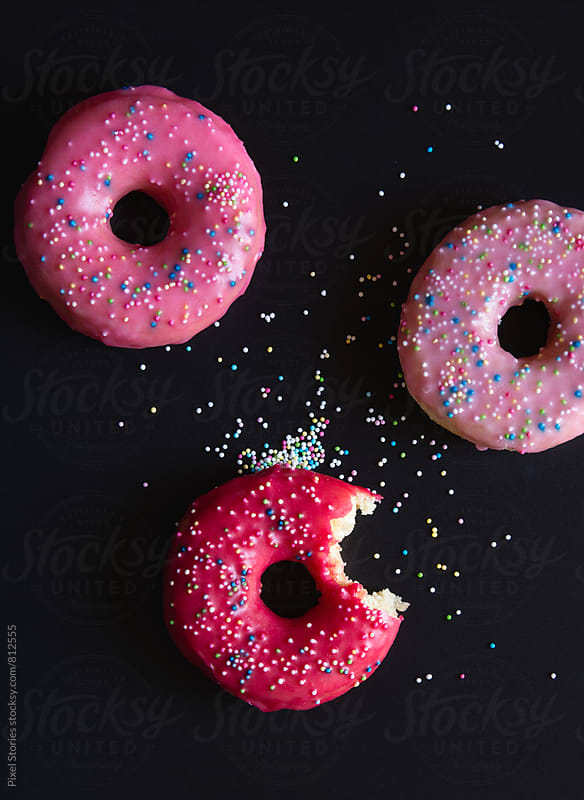 Bitten donut on dark background by Pixel Stories for Stocksy United