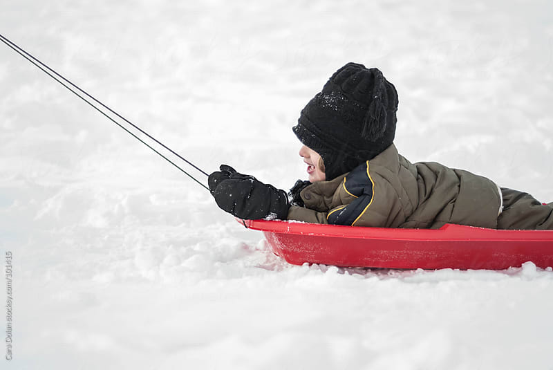 Child is being pulled in a red sled over a snow-covered hill by Cara Dolan for Stocksy United