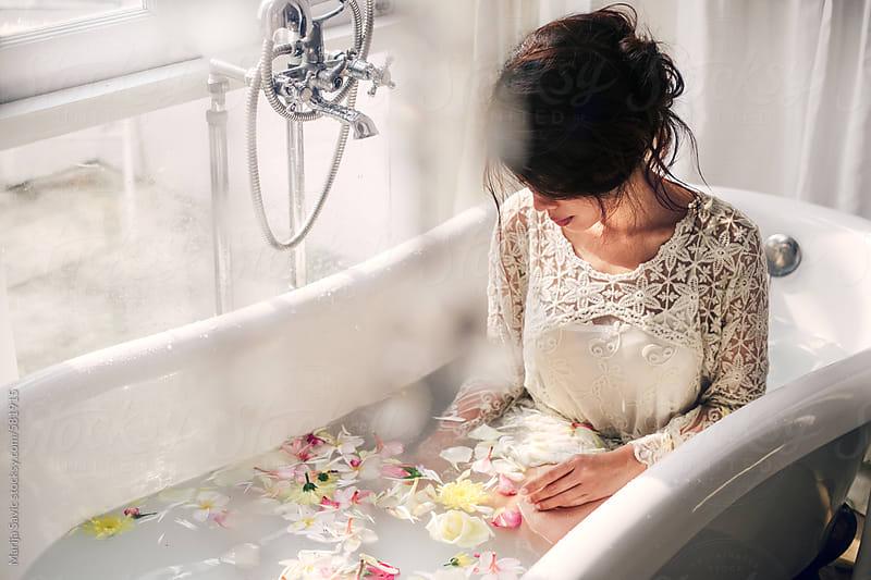 woman sitting in bathtub filled with flowers by marija savic