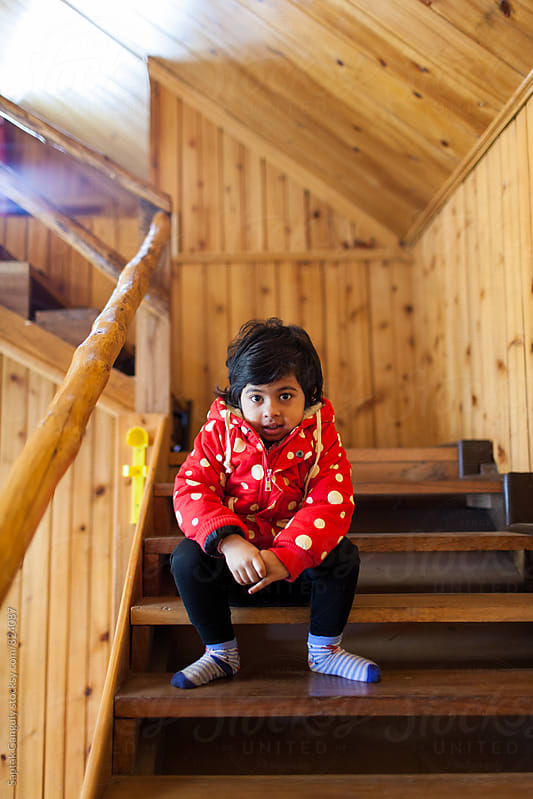Child in red jacket sitting on the wooden staircase by Saptak Ganguly for Stocksy United