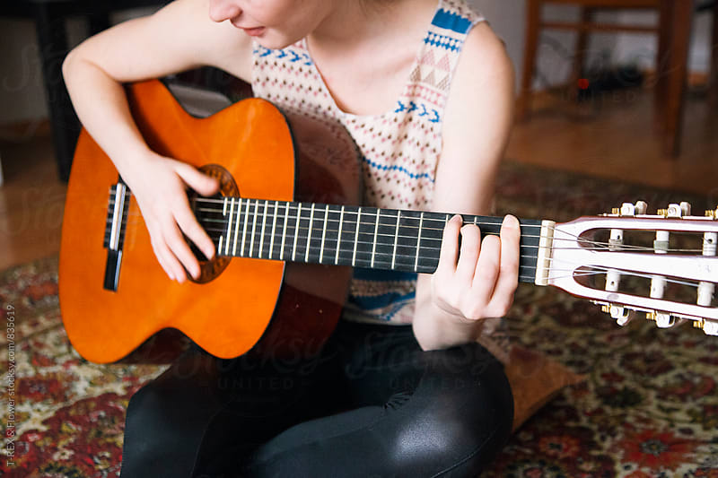 Young woman playing the guitar by Danil Nevsky for Stocksy United