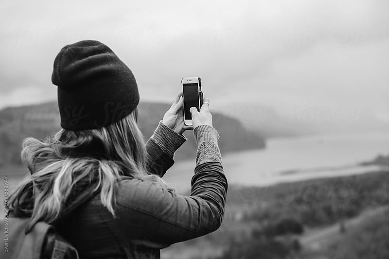 Young Woman Taking Photo With Phone On Cliff by Evan Dalen for Stocksy United
