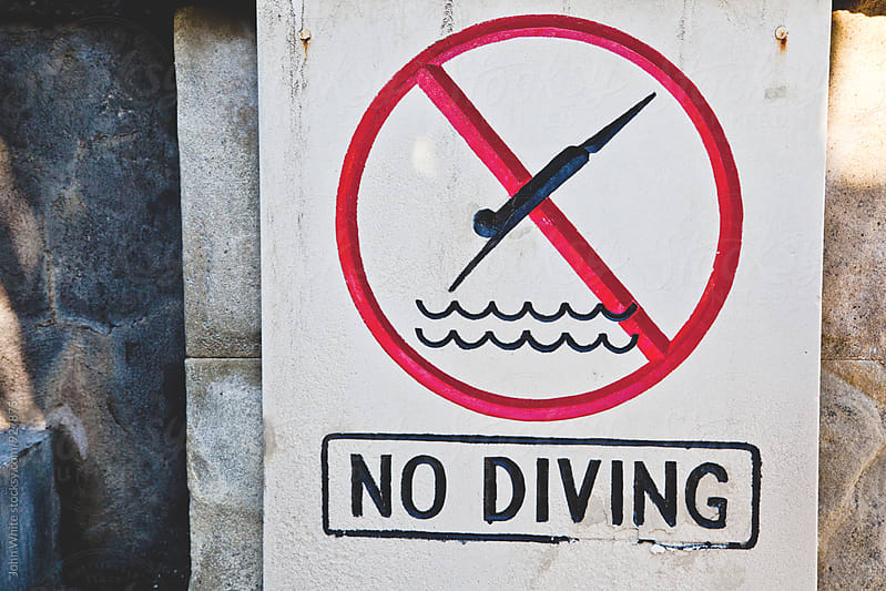 No diving sign next to a swimming pool.  by John White for Stocksy United
