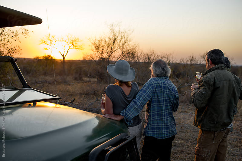 Friends enjoying the sunset by Bruce and Rebecca Meissner for Stocksy United