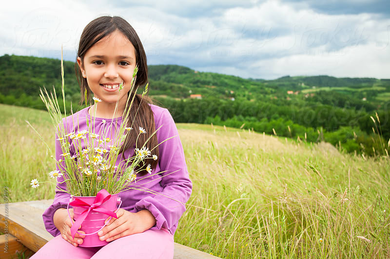 Cute girl holding wild flowers in the meadow. by Mosuno for Stocksy United
