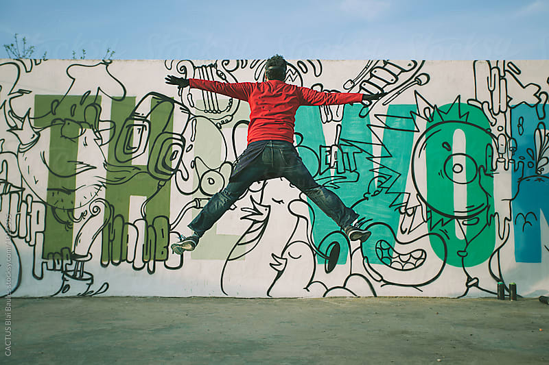 Man jumping in front of a graffiti wall by Blai Baules for Stocksy United