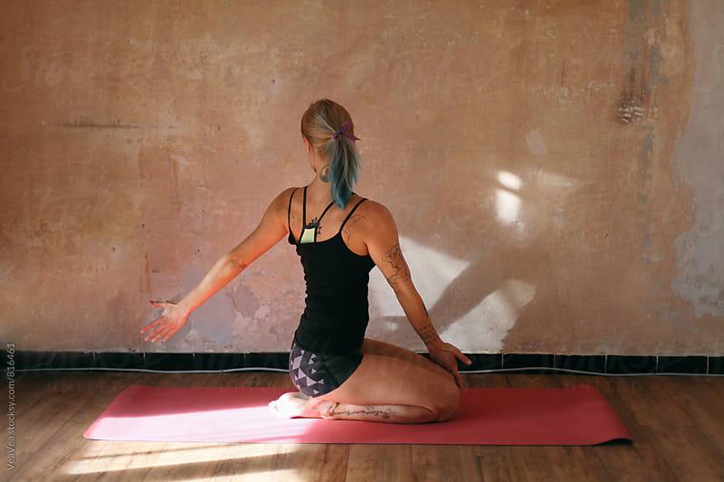 Tattooed woman doing yoga indoor by Marija Mandic for Stocksy United