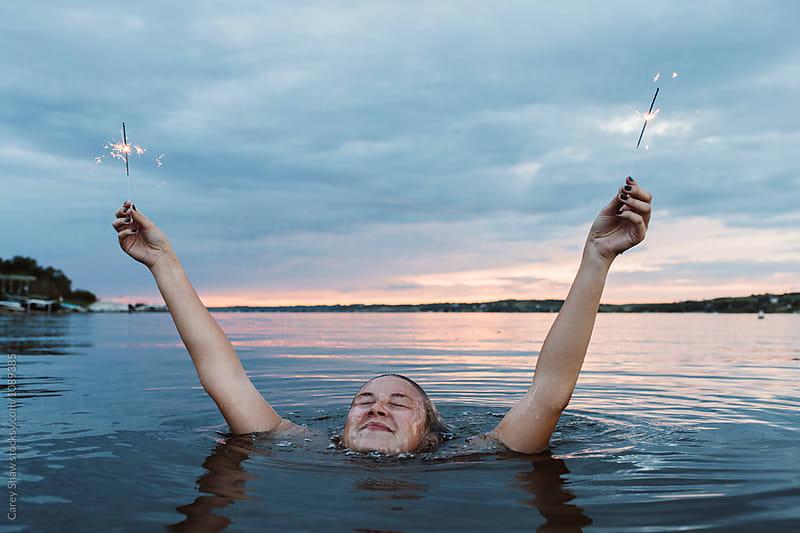 Young woman in the water holding sparklers  by Carey Shaw for Stocksy United