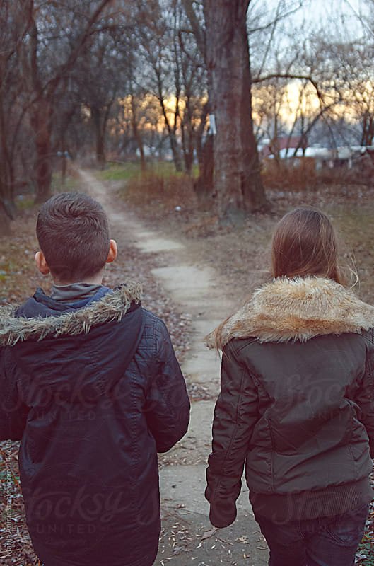 Boy and girl walking through the woods near the river in sunset by Marija Anicic for Stocksy United