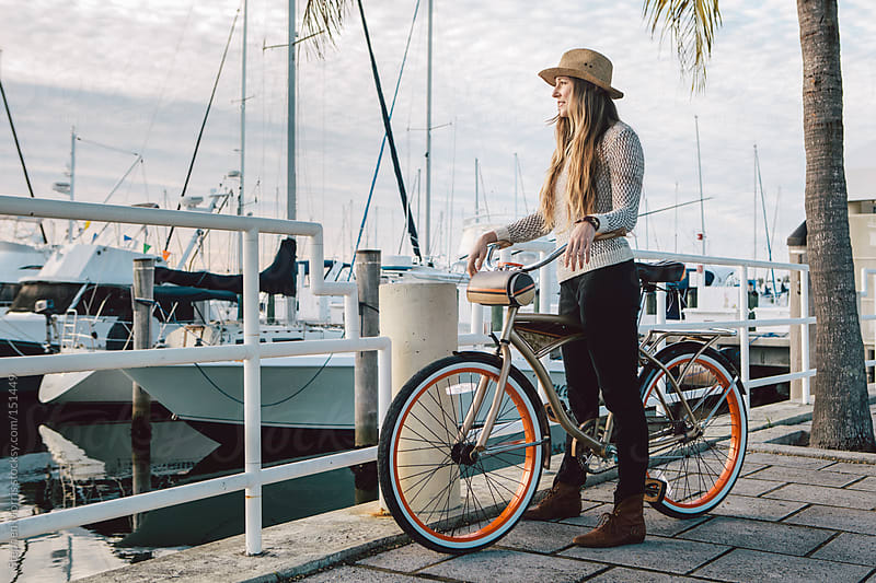 Woman with bicycle at marina by Stephen Morris for Stocksy United