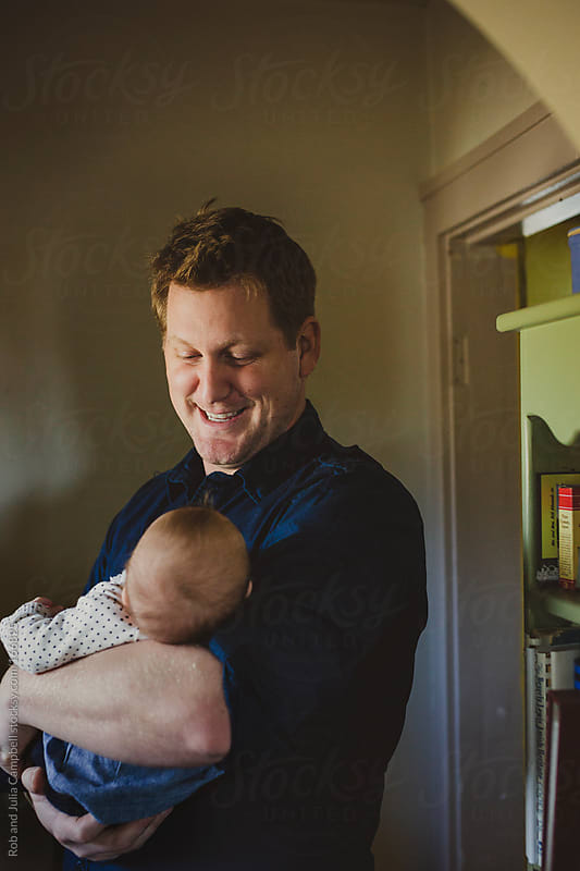 Young dad smiling as he holds new baby daughter by Rob and Julia Campbell for Stocksy United
