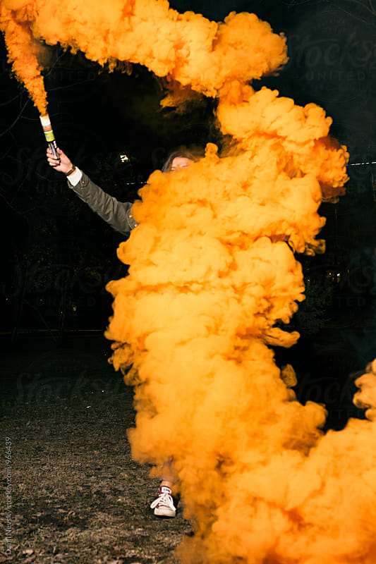 Woman holding orange smoke bomb by T-REX & Flower for Stocksy United