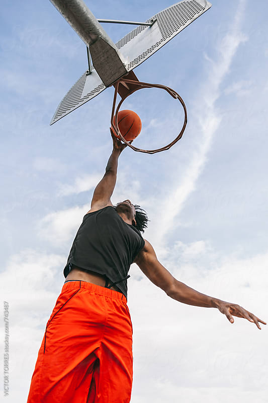 Young Afro American Man Playing in a Street Basketball Court by VICTOR TORRES for Stocksy United
