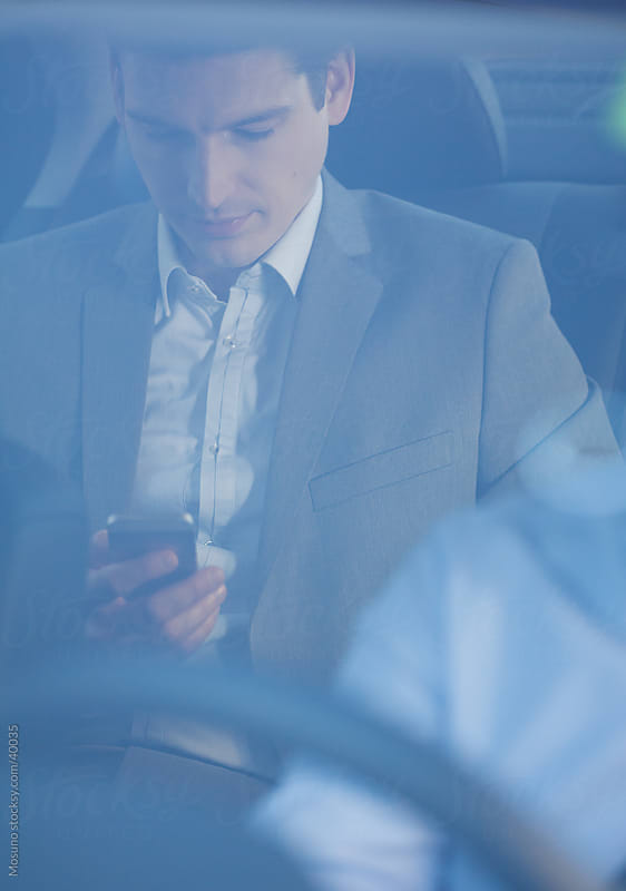 Businessman sitting in a backseat of the car and texting on the phone.  by Mosuno for Stocksy United