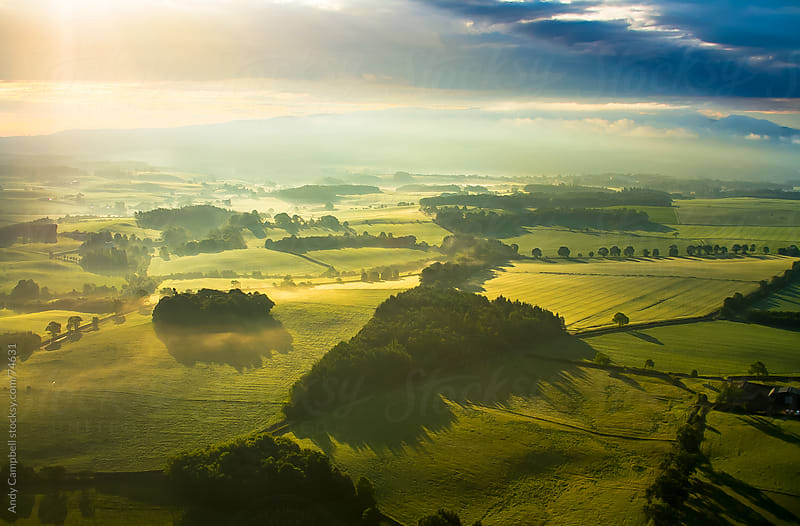 Aerial landscape view of the countryside in early morning light, with rolling hills by Andy Campbell for Stocksy United