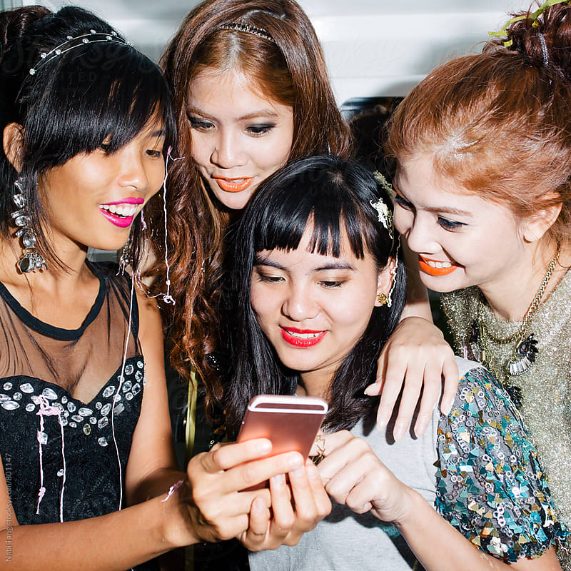 Group of women checking something on the smart phone together by Nabi Tang for Stocksy United