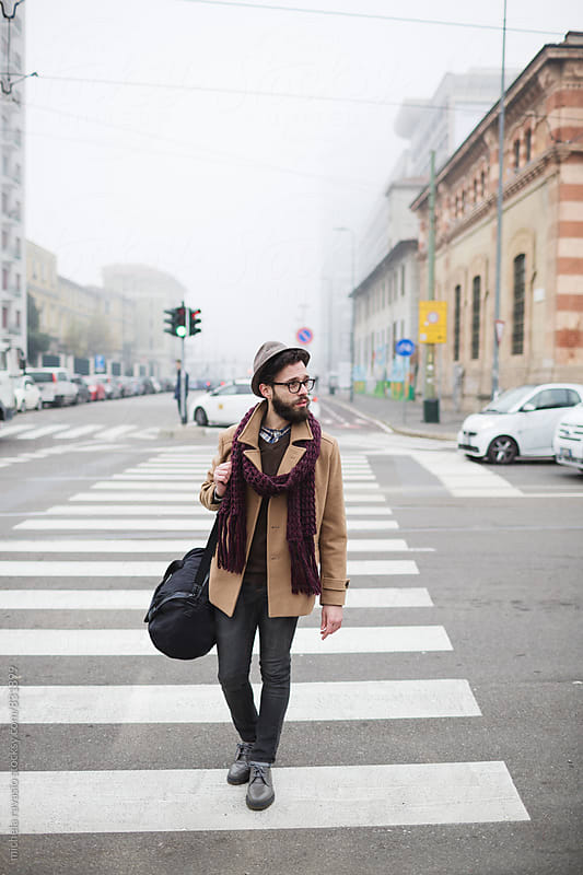 Young man crossing the pedestrian crossing by michela ravasio for Stocksy United