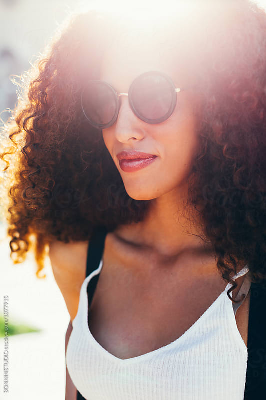 Closeup portrait of a curly brunette tourist woman outside.  by BONNINSTUDIO for Stocksy United
