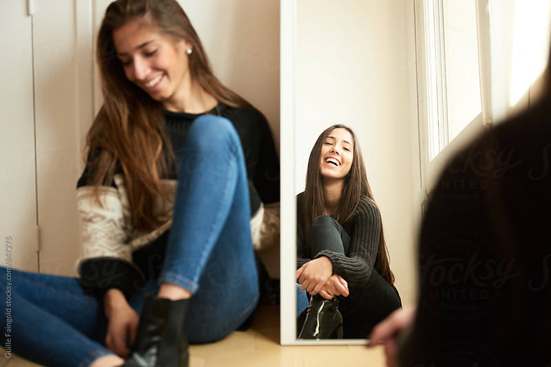 Two young girlfriends sitting on floor and having fun. by Guille Faingold for Stocksy United
