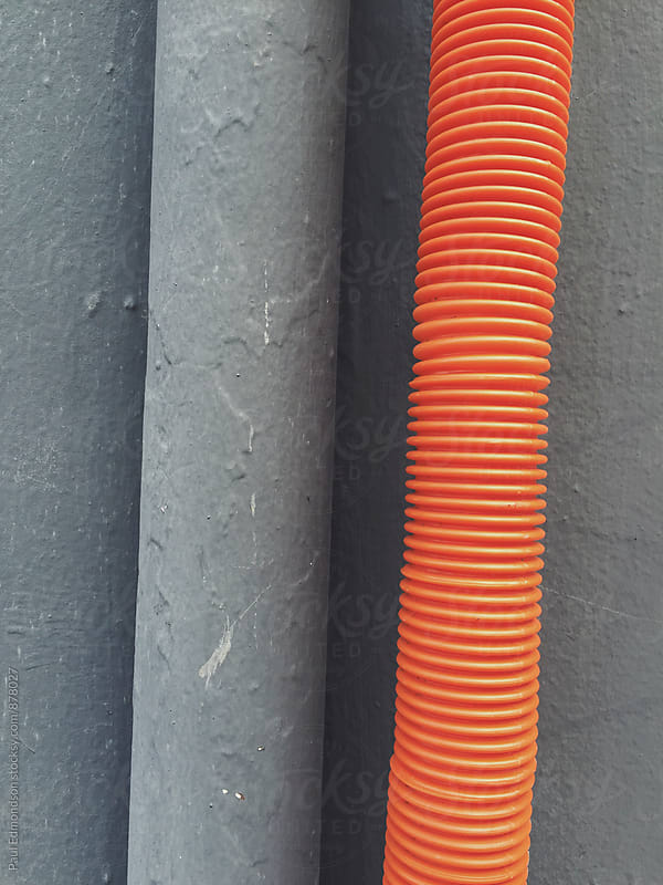 Orange and grey gutter pipes on building wall, close up by Paul Edmondson for Stocksy United
