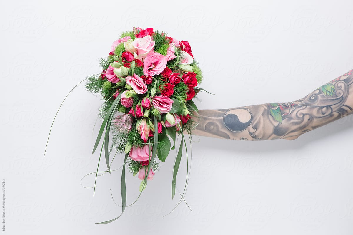 Hand With Tattoo Holding A Bunch Of Flower Stocksy United