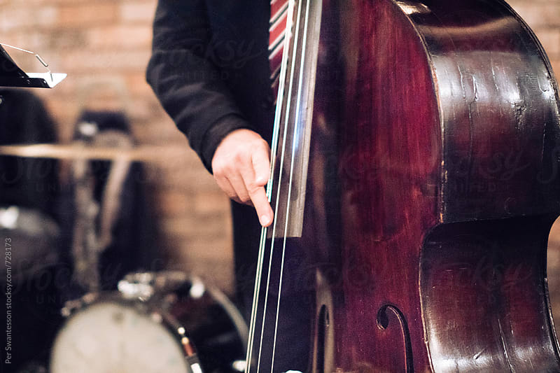 Closeup of double bass player at concert by Per Swantesson for Stocksy United