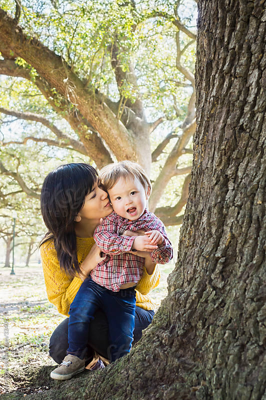 Asian mother, kissing her little boy at a park by yuko hirao for Stocksy United