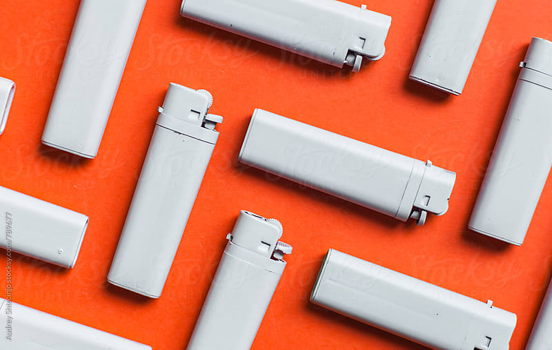 PAttern made from white lighters on red/orange background by Audrey Shtecinjo for Stocksy United
