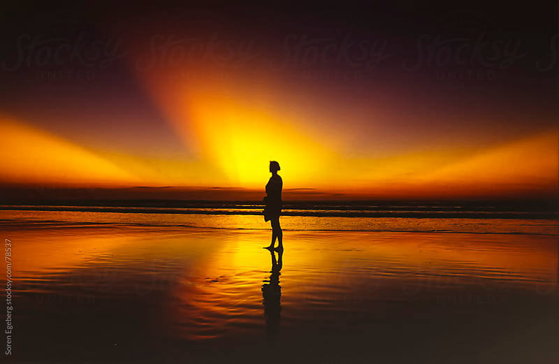 Dramatic beach sunset and woman in silhouette by Soren Egeberg for Stocksy United