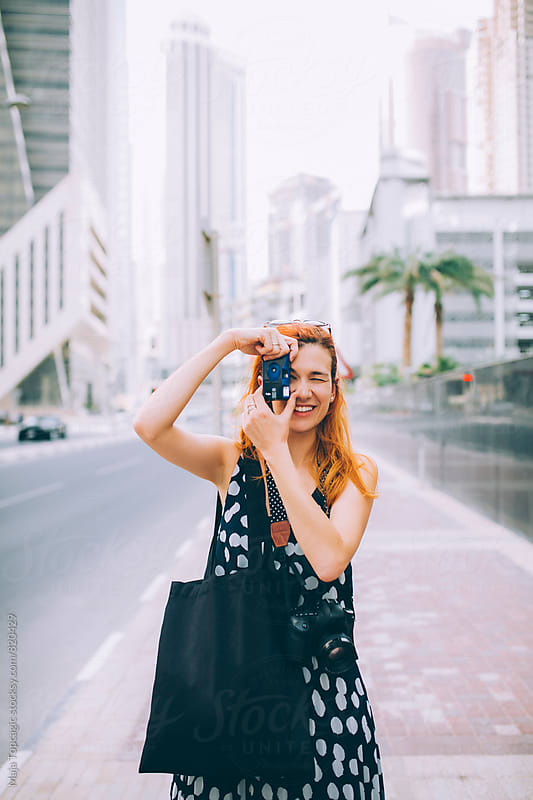 Young woman photographer taking photos with disposable camera by Maja Topcagic for Stocksy United