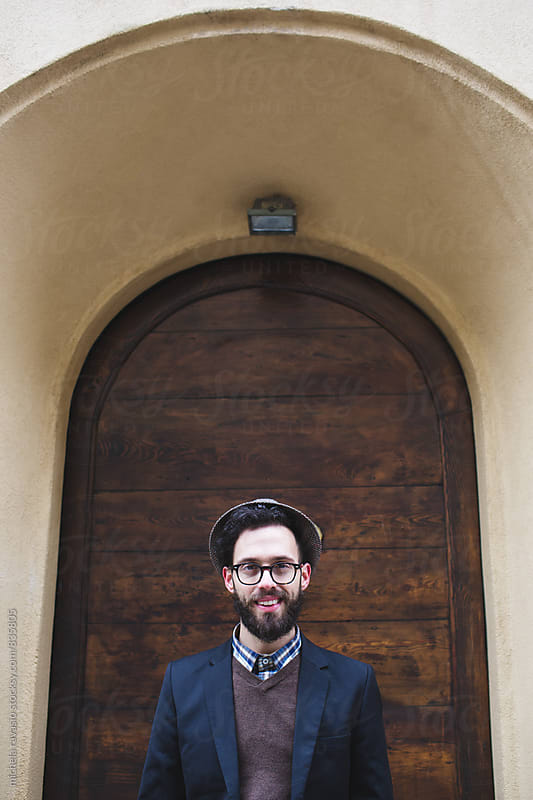 Portrait of young man smiling under an arched entrance to the house by michela ravasio for Stocksy United
