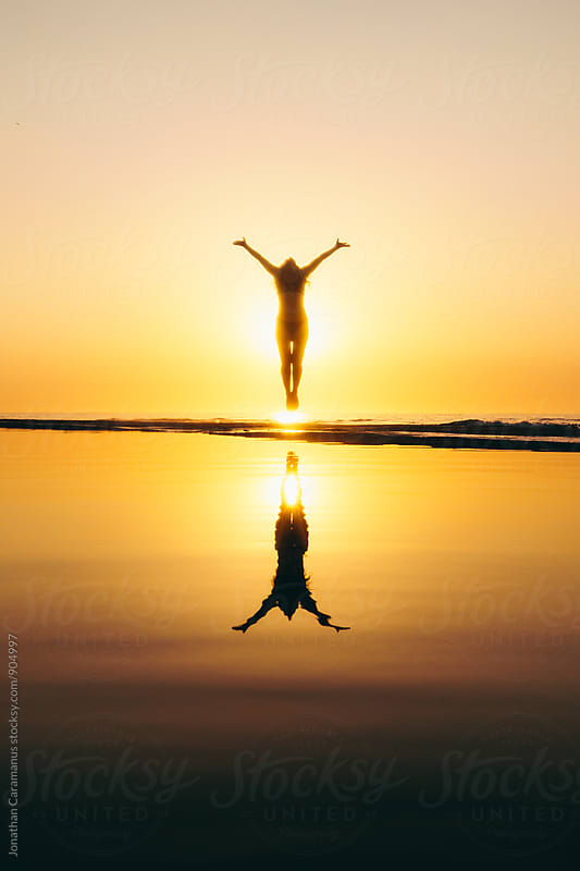 Young woman jumps for joy silhouetted by golden light at sunrise sunset with reflection in water by Jonathan Caramanus for Stocksy United