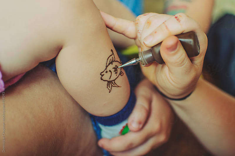 Henna tattoo fish being drawn onto toddler by Dominique Chapman for Stocksy United
