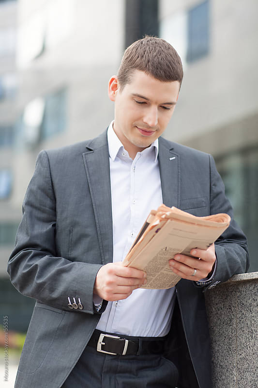Young businessman reading newspapers. by Mosuno for Stocksy United
